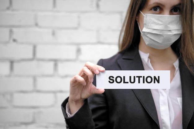 Een europees meisje dat een medisch masker draagt, houdt een bordje vast met het opschrift oplossing