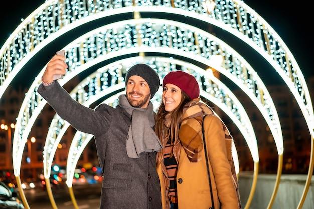 Een europees stel dat geniet van de kerstverlichting van de stad en een selfie maakt met de mobiel voor sociale netwerken