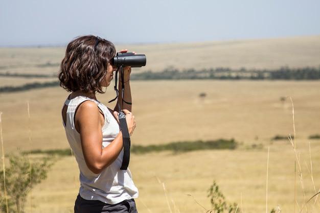 Een europees toeristenmeisje dat in het masai mara nationaal park geniet van dieren in vrijheid in de savanne. kenia, afrika