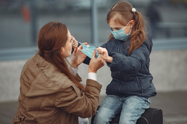 Een europese moeder in een gasmasker met haar dochter staat in de buurt van een gebouw. de ouder leert haar kind hoe ze een beschermend masker moeten dragen om zichzelf te beschermen tegen virussen