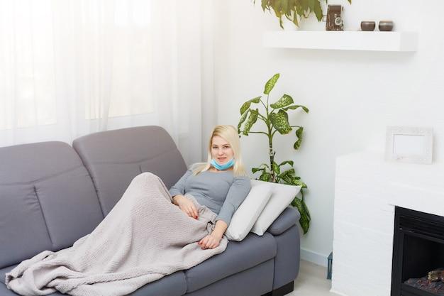 Een europese vrouw heeft een virus en is verkouden en zit met een medisch masker op.