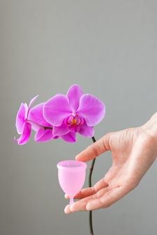 Een europese vrouw houdt een roze menstruatiecup van siliconen in haar handen