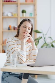 Een europese vrouw in haar thuiskantoor werkt met een laptop of kijkt naar een webinar