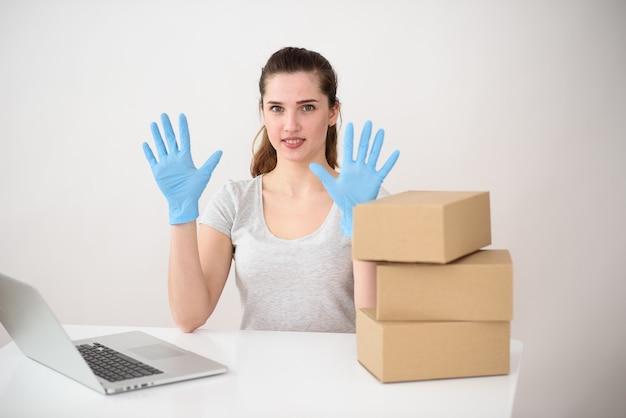 Een europese vrouw zit aan een bureau met dozen en een laptop, met beschermde handen in siliconen handschoenen