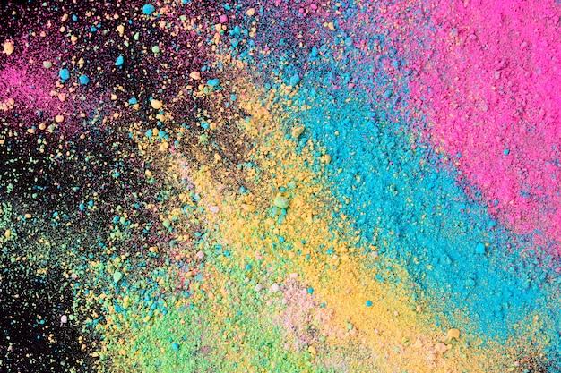 Een explosie van kleurrijk pigmentpoeder op zwarte achtergrond.