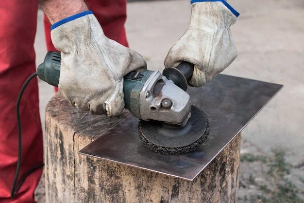 Een fabrieksarbeider in een rode overall met zijn handen in werkhandschoenen maalt een stuk plaatstaal met een oude slijper