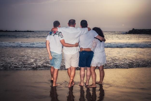 Een familie van achteren kijken ze bij zonsondergang naar de horizon in de zee