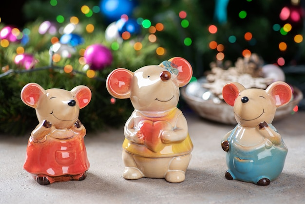 Een familie van keramische beeldjes van muizen op een kerstverlichting.