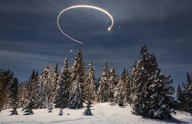 Een fantastisch magisch pad van een heldere ster aan de sterrenhemel als prachtige groene besneeuwde kerstbomen