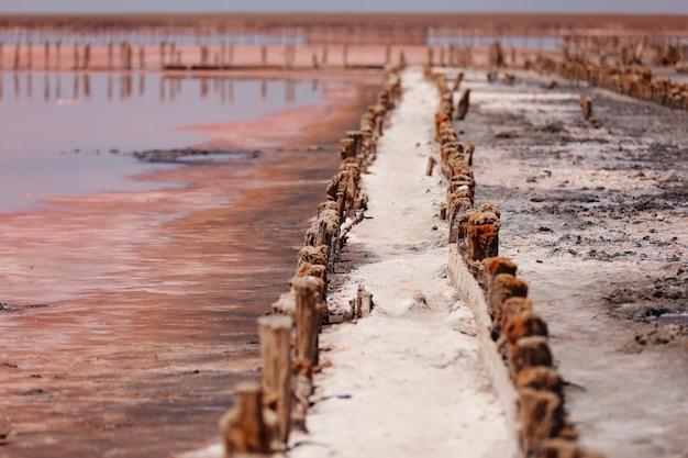 Een fantastisch roze zoutmeer met zoutkristallen op houten pilaren op zonnige dag