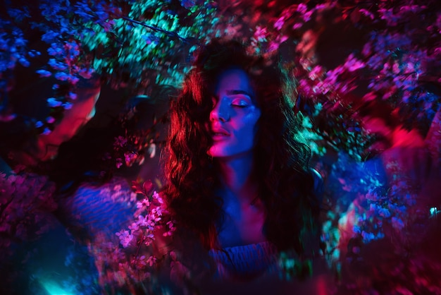 Een fantastische opname van een meisje in bloemen met veelkleurig neonlicht en fantasmagorie. het concept van fantasie, sprookjes, magie en feeën.