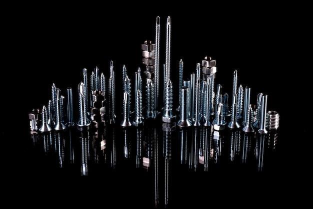 Een fantastische stad gemaakt van bouten, moeren, schroeven en zelf bezuinigingen op een zwarte ondergrond met reflectie