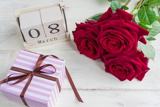 Een feestelijk geschenk, een houten kalender, een boeket rode rozen en een geschenkdoos op een houten achtergrond. het concept van felicitaties op 8 maart of wooman's dag.