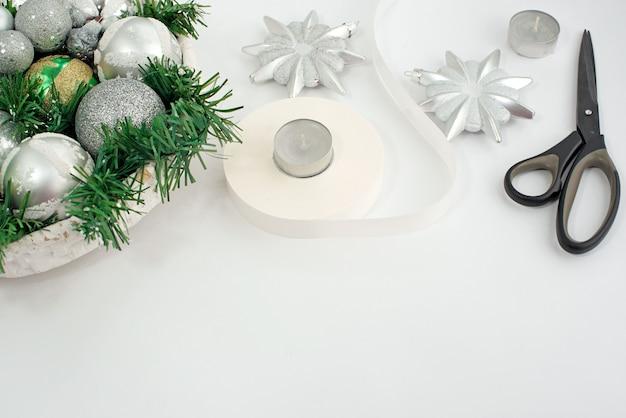 Een feestelijk kerstarrangement kunstmatige takken, glazen bollen in de mand.