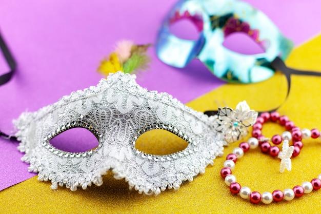 Een feestelijk, mooi wit mardi gras of carnaval masker op mooie kleurrijke document achtergrond