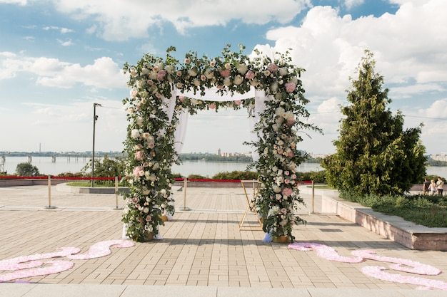 Een feestelijke chuppah versierd met verse bloemen voor een buiten huwelijksceremonie