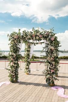 Een feestelijke chuppah versierd met verse mooie bloemen voor een buiten huwelijksceremonie