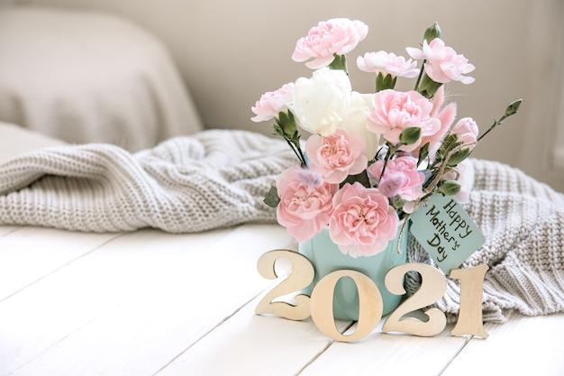 Een feestelijke compositie met verse bloemen in een vaas, het jaartal 2021 en een wens voor een gelukkige moederdag op een ansichtkaart.