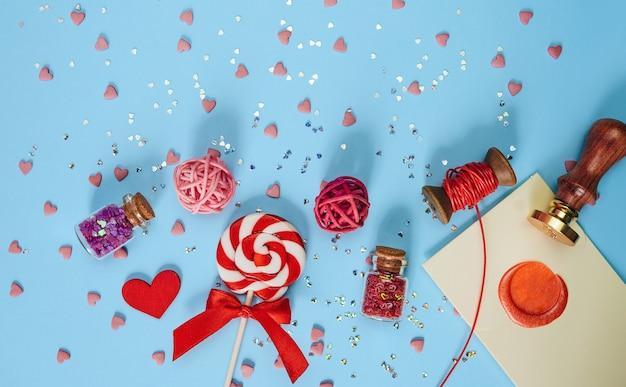 Een feestelijke lolly; brief en geschenkdoos ligt op een blauwe achtergrond. concept van liefde en viering van valentijnsdag. bovenaanzicht; plat leggen.