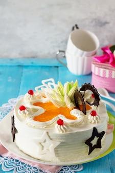 Een feestelijke taart met slagroom versierd met chocolade en romige room op een blauwe achtergrond