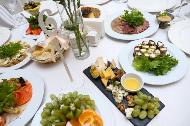 Een feestelijke tafel serveren met een verscheidenheid aan gerechten. stukken kaas van verschillende variëteiten, honing in een glazen kom, fruit, groenten en noten op een keramisch zwarte schaal op een lichttafel.