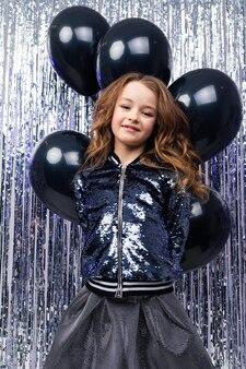 Een feestje. jonge stijlvolle blanke meisje staat met zwarte helium ballonnen op een glanzende vakantie klatergoud muur