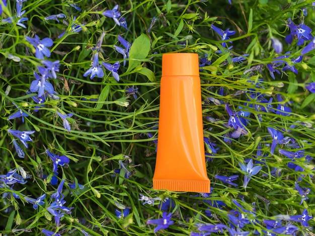 Een fel oranje tube crème op een achtergrond van kleine bloemen.
