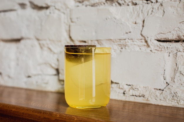 Een felgele cocktail met ijs in een lowball-glas van rotsen gegarneerd met passievrucht