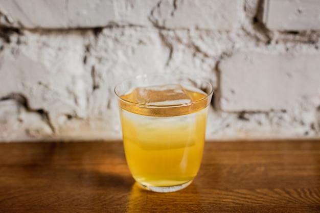 Een felgele cocktail met ijs in een lowball-glas