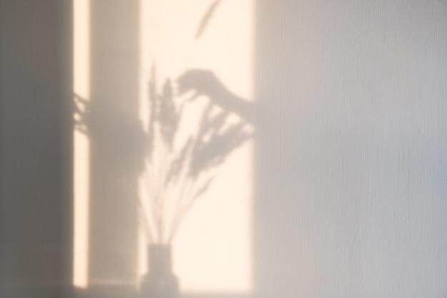 Een felle schaduw van een vrouwenhand voegt een puntje droog gras toe aan een boeket gedroogde bloemen tegen een lichte muur