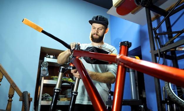 Een fietsenmaker monteert een mountainbike in zijn werkplaats. een man met een pet op met een baard. de monteur schuift het wiel naar het fietsframe