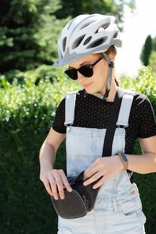 Een fietser met zonnebrandcrème onderzoekt haar heuptas. slimme band. weelderige groene achtergrond