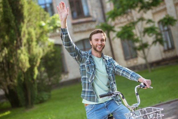 Een fietstocht. een foto van een jonge man in een geruit hemd op een fiets