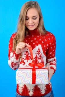 Een fijne wintervakantie gewenst! mooi meisje opent kerstcadeau van haar vriendje. verticaal portret; geïsoleerd op een heldere blauwe achtergrond