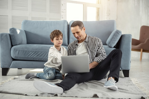 Een film kijken. leuke vrolijke blonde jongen lachend en zittend op de vloer met zijn vader en zij met behulp van hun laptop