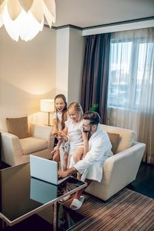 Een film kijken. vader en twee meisjes kijken naar iets op een laptop