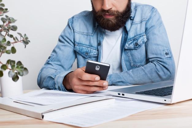 Een filmeffect. portret van de gebaarde mens in het overhemd die van jean smartphone in zijn hand hoding terwijl het werken met documenten in bureau met gezellig binnenland. bijgesneden portret van succesvolle zakenman mobiel gebruiken.