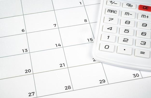 Een financieel concept met een rekenmachine op de kalender.
