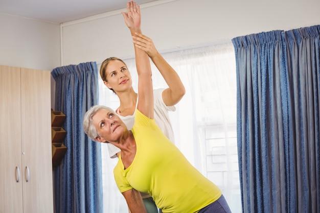 Een fitness instructeur helpt senior oefeningen te doen