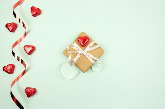 Een flatlay van een geschenkdoos en snoep in de vorm van de harten voor valentijnsdag