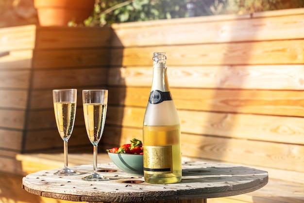 Een fles champagne met twee glazen en aardbeien op hout