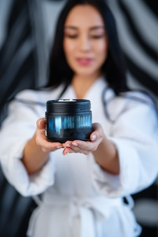 Een fles cosmetica in de handen van een meisje dat in bokeh is