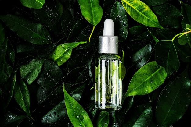 Een fles cosmetische olie op natte bladeren