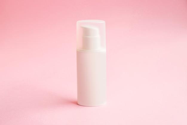 Een fles crème met dispenser op roze achtergrondmodel. beauty spa medische huidverzorging en cosmetische lotioncrème
