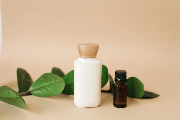 Een fles crème voor huidverzorging voor het gezicht of lichaam, een bruine glazen fles met olie en bladeren van zamiokulkas op een beige achtergrond. biologische cosmetische producten