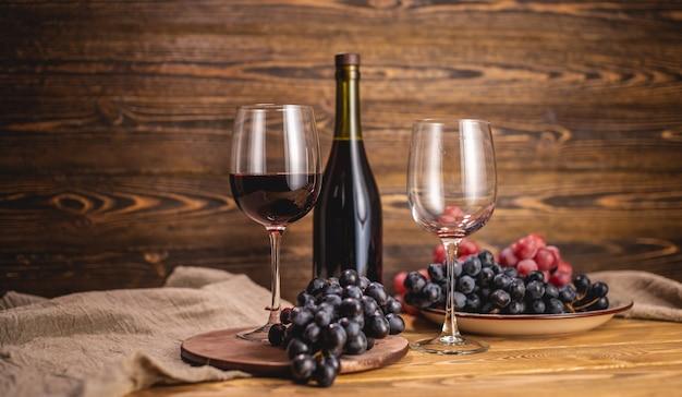 Een fles droge rode wijn met een glas en een tros druiven op een houten tafel