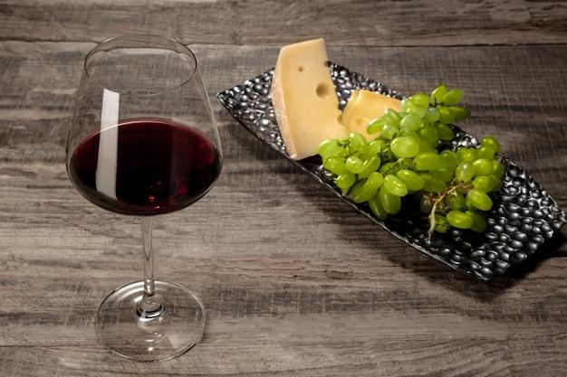 Een fles en een glas rode wijn met fruit over houten tafel