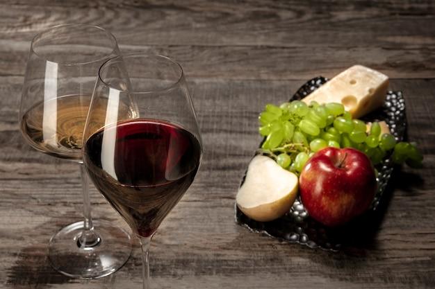 Een fles en glazen rode en witte wijn met fruit