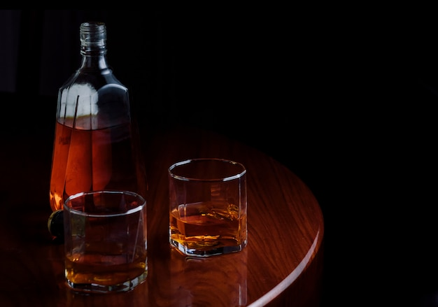 Een fles en glazen sterke drank op houten lijst