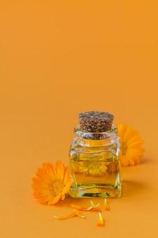 Een fles etherische olie van een potgoudsbloem met verse calendula-bloemen op sinaasappel